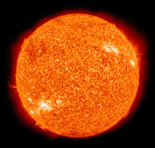 A closeup of the sun, orange with several solar flares