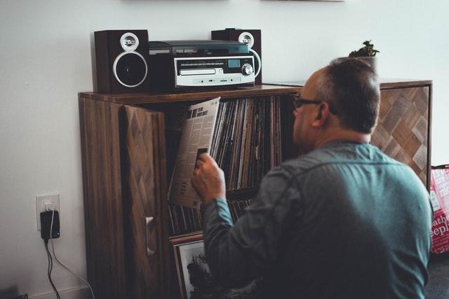 A man placing a vinyl record into his collection