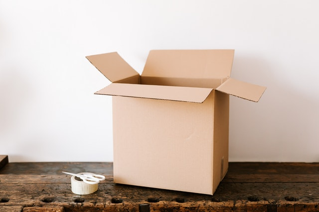 A cardboard box with tape and scissors